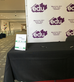 "SXSWEdu signing table, ParaEducate propped up on corner left of table with black table cloth in front of white vinal sign with purple ""SXSWEdu"" logo. Pen on table top next to hallway"